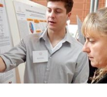 Dr. Lewis and student looking at a poster presentation.